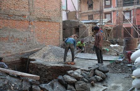 BHAKTAPUR, NEPAL - JANUARY 23, 2017: Nepalese men working hard in road building after the earthquake damage in Kathmandu valley Редакционное