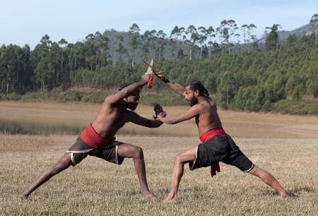 Indian fighters performing Aayudha Payattu (Weapon Combat) during Kalaripayattu Marital art demonstration in Kerala, South India Foto de archivo