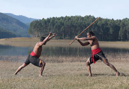 Indian fighters with bamboo stick performing Kalaripayattu Marital art demonstration with bamboo stick in Kerala state, South India