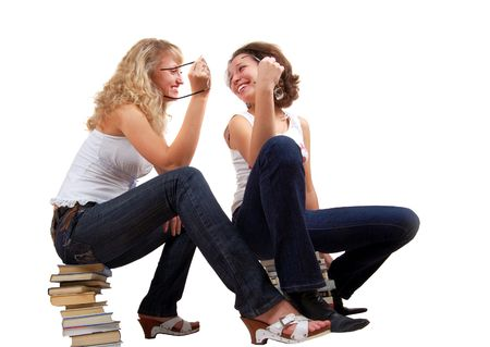 two girl talking and laughing, sitting on books. Isolated on white.