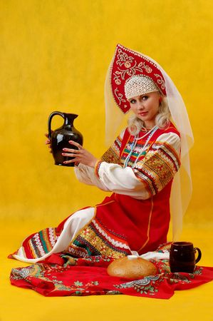 a beautifull woman in a folk russian dress on yellow background