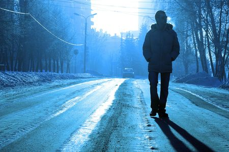 solitude: alone silhouette of the guy run on the winter road Stock Photo