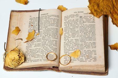 vangelo aperto: anelli e sbiadito fiore sulla vecchia Sacra Bibbia  Archivio Fotografico