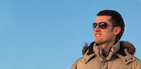 young man in winter clothers with sunglasses, isolated on blue Stock Photo - 2514129