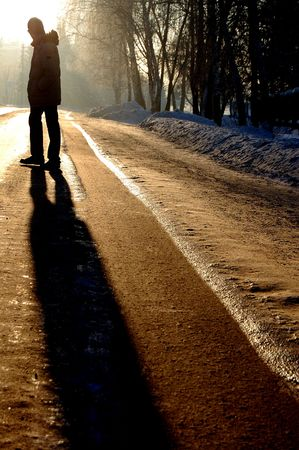 alone guy standing on the winter road