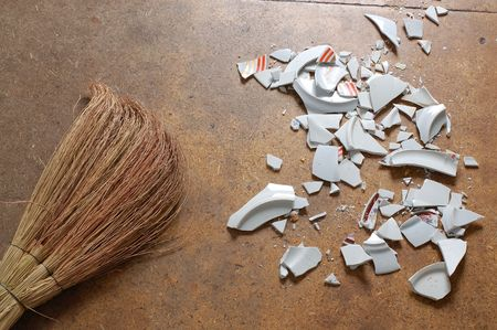 besom: pieces of broken dish and a bessom, laying on the floor
