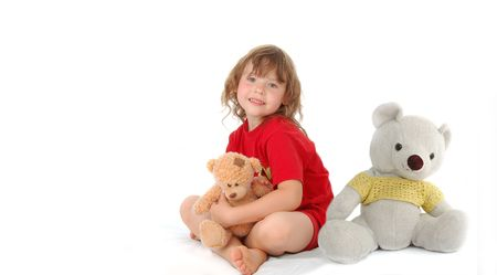 joyful young girl sitting on the floor with two teddy bears photo