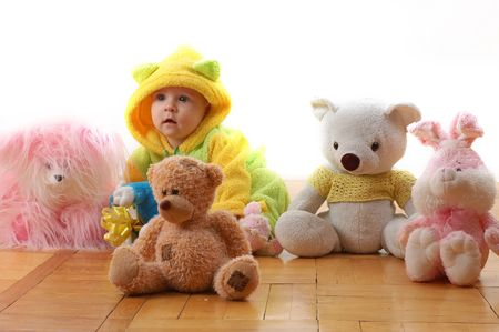 a baby sittig between toys and looking like one of theese toys