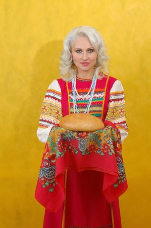 Russian woman in a folk russian dress Holds a bread on yellow background