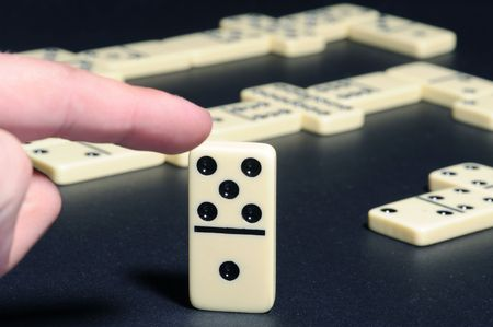 unsure: Close-up of human fingers push a dominoes. Business concept Stock Photo