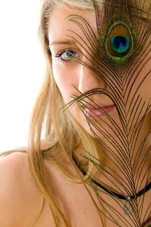 Close-up portrait of beautiful girl, peacock a feather closes eye  photo