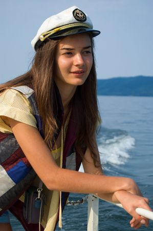 Portrait of captain. Beautiful brunette young girl on a boat photo