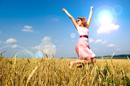 Happy woman wearing sunglasses jumping in golden field