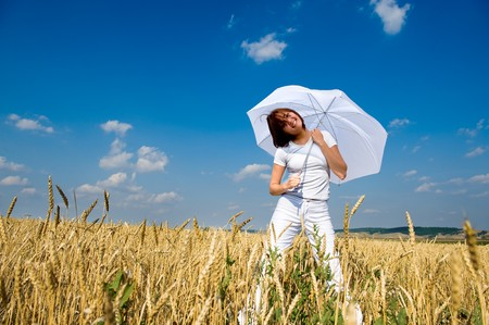 Beautiful young woman under blue sky with umbrella in the field. Smiling face Stock Photo