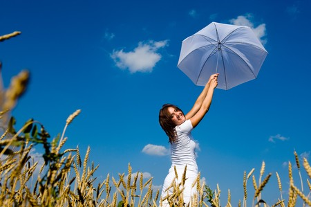Beautiful young woman under blue sky with umbrella in the field. Smiling face 스톡 콘텐츠