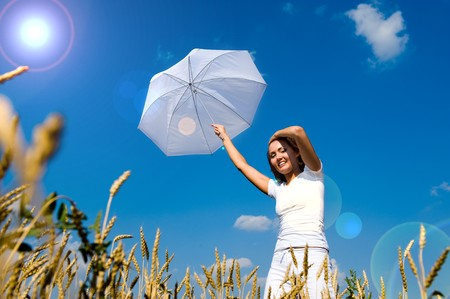 Beautiful young woman under blue sky with umbrella in the field. Smiling face Stockfoto