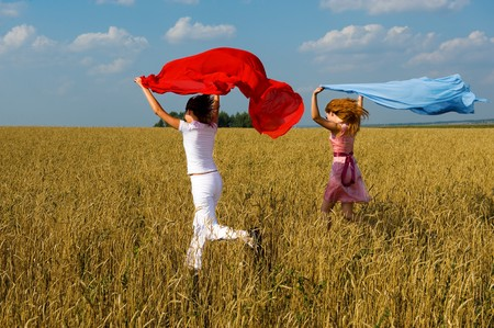 Two young beautiful woman running on the field with a red and blue scarfs Stock Photo - 4116874