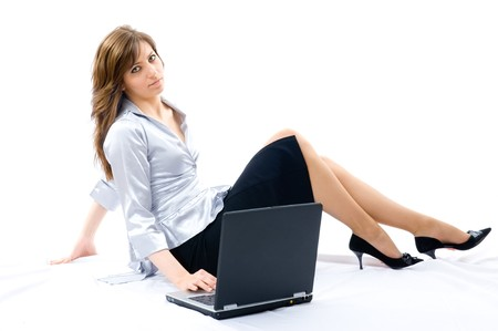 Young businesswoman working with laptop. Lying on the floor. Isolated on white background photo