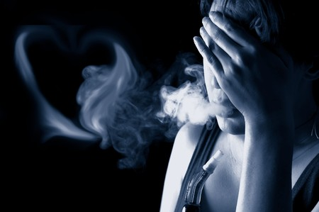 Portrait of sad woman smoking in the darkness photo