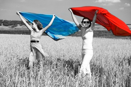 Two young beautiful woman running on the field with a red and blue scarfs Stock Photo - 4503137