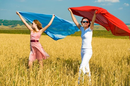 Two young beautiful woman running on the field with a red and blue scarfs Stock Photo - 4503139