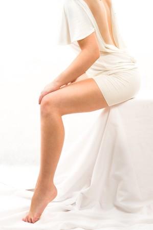 fem: beautiful woman sitting on something white. Isolated over white