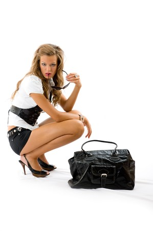 Attractive girl with sexy dress and big fashion bag sitting on the floor. Isolated on white Stock Photo - 4569864