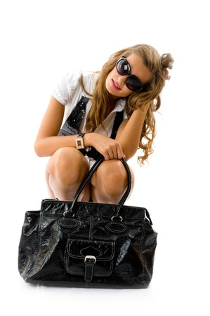 Attractive girl with sexy dress and big fashion bag sitting on the floor. Isolated on white photo