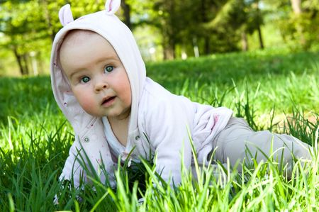 Little baby on green grass in summer meadow