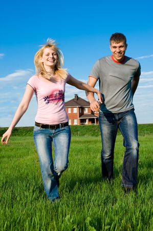 hand holding house: Happy couple running outdoors outside their home Stock Photo