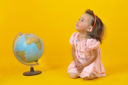 Baby and globe on the yellow background photo