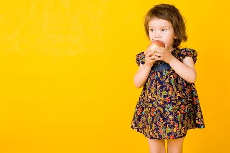 Little girl with apple isolated on yellow  background