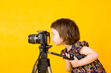 Portrait of baby girl holding camera isolated on yellow background