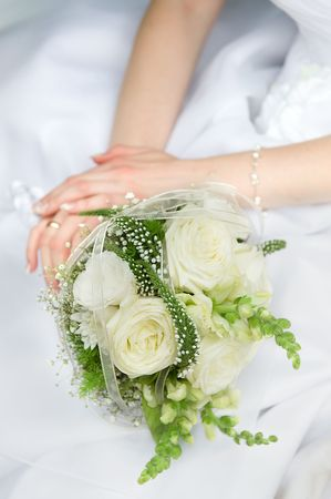 Bride hands on the wedding dress close-up