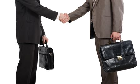 Two businessmen holding briefcases and shaking hands over white background photo