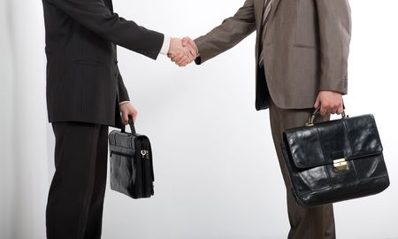 Two businessmen holding briefcases and shaking hands  photo
