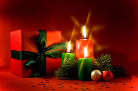 Burning xmas candle and little gift box. Christmas decorations of the cross filter effect  Stock Photo