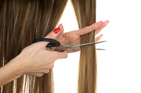 Close-up hands holding scissors trying to cut long hair photo