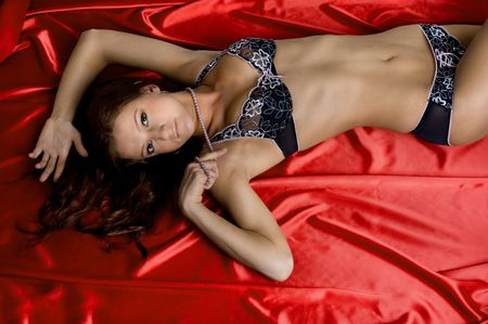 Picture of beautiful woman in sexy lingerie, lying on red fabric