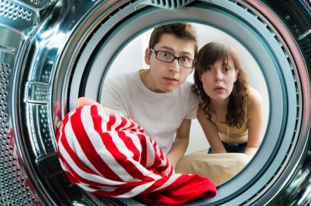 dryer: Funny couple loading clothes to washing machine. From inside the washing machine view. Stock Photo