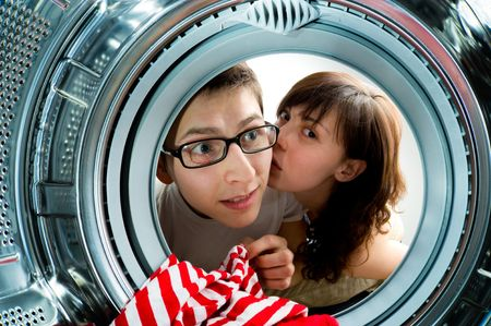 Funny couple loading clothes to washing machine. From inside the washing machine view. 免版税图像