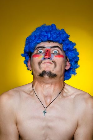 studio b: Close-up portrait. Clown in a blue wig, expressing surprise. Yellow background Stock Photo