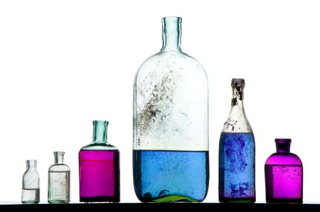 old perfumer bottles with colorful liquid on white