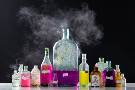Magic spells in antique bottles over black background and smoke