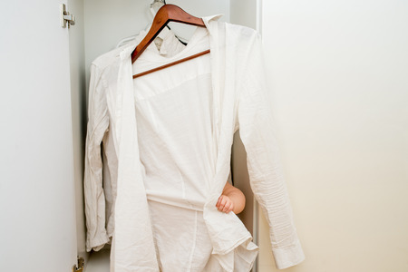 baby wardrobe: little child trying on clothes. He wants to dress white shirt