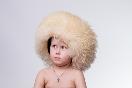 frowned: Portrait of a boy wearing funny furry winter hat Stock Photo