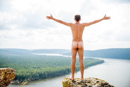 Feel the freedom. Naked man on a high mountain
