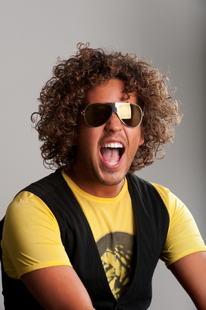 Cheerful young man with beautiful curls have fun Stock Photo