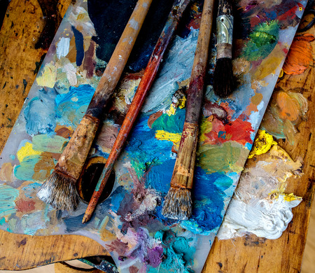 paints and brushes on a wooden palette
