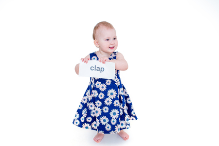 Little girl holding a card with the word clap